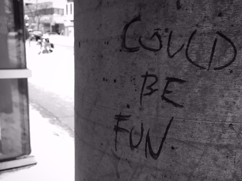 A cement pole with 'could be fun' on it in black marker grafitti