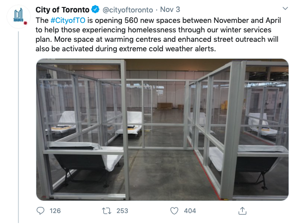 "A screen shot of a tweet by @cityoftoronto. It reads, ""The City of Toronto is opening 560 new spaces between November and April to help those experiencing homelessness through out winter services plan. More space at warming centres and enhanced street outreach will also be activated during extreme cold weather alerts."" There is also an imge which shows a large, warehouse like room in which glass barriers separate cots. The rooms are about twice the size of the cots. The glass walls provide no privacy. The cots resemble lawn chairs and feature a thin mattress."